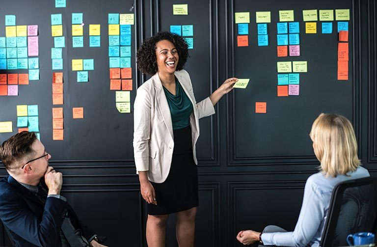 Woman putting post it notes on board.