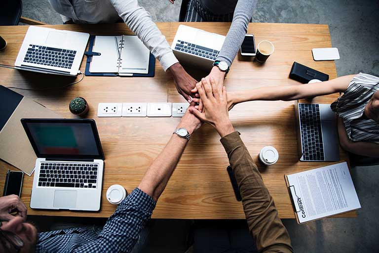 Employees touching hands in center of office desk.